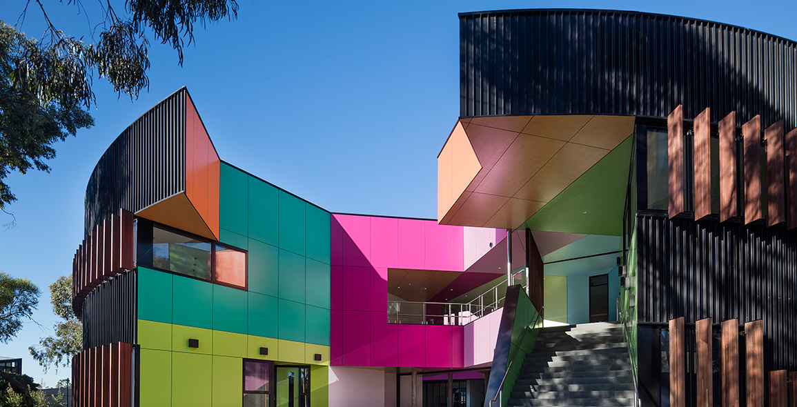 From the opposite corner, black fins circulate the circular building, unassuming of the burst of vibrant colours